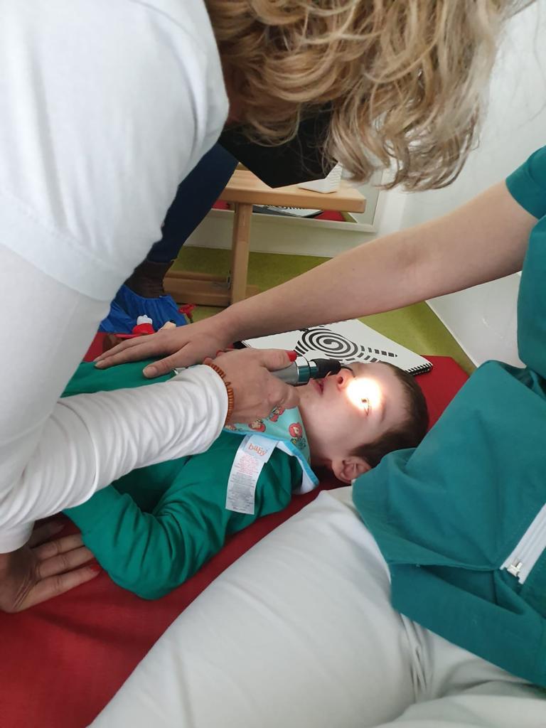Pilar Vergara realizando un diagnostico de optometría conductual a un niño discapacitado en Rumanía